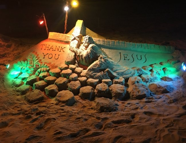 sand sculpture of jesus on the beach with lights